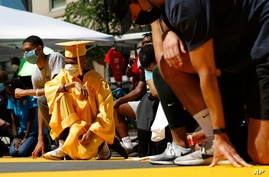 Brian Gardener, left, wears his middle school graduation cap and gown as he kneels with demonstrators in remembrance of George…