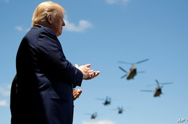 President Donald Trump applauds as Army helicopters fly overduring the Class of 2020 at a commencement ceremony on the parade field, at the United States Military Academy in West Point, N.Y., June 13, 2020.