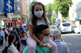 A man wearing a face mask to protect against the new coronavirus, holds a young girl on his shoulders, in Ankara, Turkey