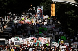 People march down the street towards the Georgia state capitol to protest against the mistreatment of black people and to press…