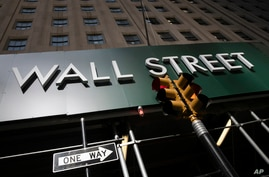 A sign for a Wall Street building is shown, Tuesday, June 16, 2020. Stocks are rising sharply in early trading on Wall Street…