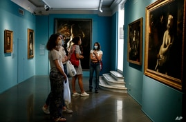 Visitors admires paintings part of the exhibition The Time of Caravaggio, Masterpieces of the Roberto Longhi collection, on display at the Capitoline Museums in Rome, June 16, 2020.