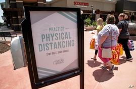 Shoppers carry their bags past a hand sanitizing station at the Village Pointe shopping mall in Omaha, Neb., Tuesday, June 16,…