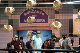 Costumers wear masks amid the new coronavirus pandemic inside the Madureira market where hats hang as decoration in Rio de…