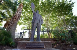 In this June 17, 2020, photo, a statue depicts a man holding the state law that made Juneteenth a state holiday