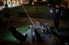 People film the only statue of a Confederate general, Albert Pike, in the nation's capital after it was toppled by protesters and set on fire in Washington early Saturday, June 20, 2020.