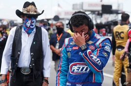 Driver Bubba Wallace, right, is overcome with emotion as he and team owner Richard Petty walk to his car in the pits of the…