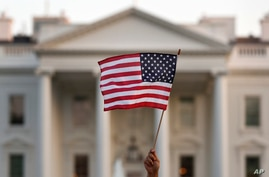 FILE - In this Sept. 5, 2017, file photo, a flag is waved outside the White House, in Washington. The Trump administration is…