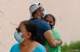People embrace on he street as they wait for the all-clear to return to their apartment after an earthquake in Mexico City,…