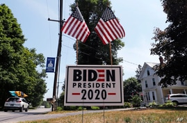A car passes a yard displaying a campaign sign for Democratic presidential candidate, former Vice President Joe Biden on…