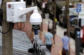 FILE - In this April 14, 2014, file photo, a surveillance camera is attached to a light pole along Boylston Street in Boston…