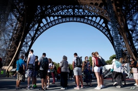 People queue up prior to visit the Eiffel Tower, in Paris, June 25, 2020.