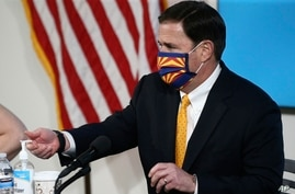 Arizona Republican Gov. Doug Ducey uses hand sanitizer as he wears a face covering prior to speaking at a presser