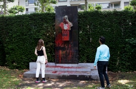 A couple stop to look at a bust of Belgium's King Leopold II, which has been damaged by red paint, graffiti and cement, at a park in Ghent, Belgium, June 19, 2020.