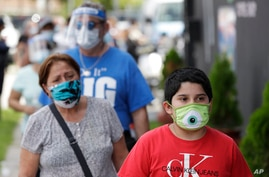 People, social distancing and wearing masks to prevent the spread of the new coronavirus, wait in line at a mask distribution…