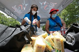 Volunteers Vanessa Sheffield, left, and Anakarina, who declined to give her last name, load food into bags at a food and mask…