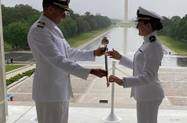 US Navy RDML (Sel.) Putnam Browne presents his daughter, Navy ENS Francesca Browne, with a family sword during her commissioning ceremony at the Lincoln Memorial. (Browne Family May 2020)