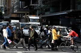 People cross a traffic intersection in the central business district of Sydney, Australia, June 18, 2020.
