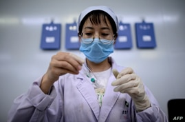 FILE - A technician examines a vile at a laboratory in Shenyang, in China's northeast Liaoning province, June 9, 2020.