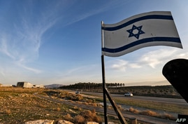 FILE - An Israeli flag stands by a road near the Israeli settlement of Shlomtzion in the Jordan valley of the occupied West Bank, Jan. 27, 2020.
