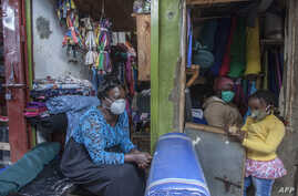 A woman and her child wear face masks as preventive measure against the COVID-19, in her shop inLilongwe City market in Lilongwe, Malawi, May 18, 2020.