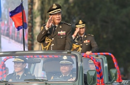 FILE - Cambodian Prime Minister Hun Sen (L) salutes, along with his son, Lt. Gen. Hun Manet (background) during an inspection of troops at a ceremony in Phnom Penh, Cambodia, Jan. 24, 2019.