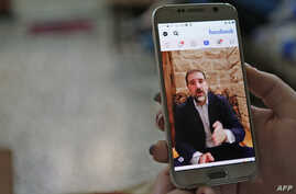 FILE - A woman watches a Facebook video of Syrian businessman Rami Makhlouf on her mobile phone in Syria's capital Damascus, May 11, 2020.