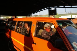 FILE - A taxi operator drives commuters in Pretoria, South Africa, June 1, 2020. Taxi drivers in the country's financial hub Gauteng went on strike to demand goverment support during the coronavirus pandemic.