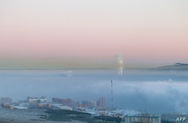 FILE - Smog covers the Siberian industrial city of Krasnoyarsk, Russia, Jan. 4, 2018. The Siberian town of Verkhoyansk recently reported an unprecedented temperature of 38 degrees Celsius.
