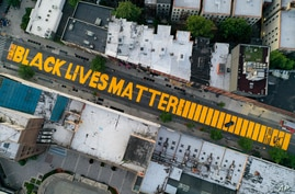 "FILE - A giant ""Black Lives Matter"" sign is painted on Fulton Street, in the Brooklyn borough of New York City, June 15, 2020."