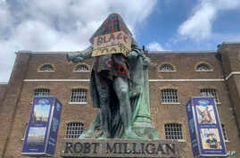 The statue of Robert Milligan, a noted West Indian merchant, slaveholder and founder of London's global trade hub, West India Docks, stands covered in a sack-cloth and sign reading Black Lives Matter, outside the Museum of London Docklands, June 9, 2020.