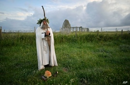 An Archdruid performs a ritual near to the cordoned off Stonehenge as a small group of people gathered to celebrate the Summer…