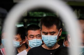 Commuters wearing protective face masks to help curb the spread of the coronavirus line up to board a bus at a terminal in Beijing, June 22, 2020.