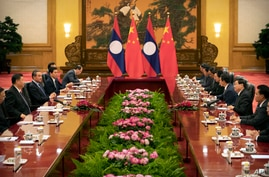 FILE - Chinese President Xi Jinping, left, speaks as Laos' Prime Minister Thongloun Sisoulith, second from right, listens during a meeting at the Great Hall of the People in Beijing, Jan. 6, 2020.