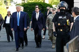 President Donald Trump departs the White House to walk to St. John's Church in Washington, June 1, 2020. Defense Secretary Mark Esper is to Trump's right.