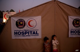 FILE - Rohingya refugee children from Myanmar are seen in front of a Malaysian field hospital near Cox's Bazar, Bangladesh, Jan. 27, 2018. The IFRC has opened two such facilities in Cox's Bazar to help fight the spread of COVID-19.