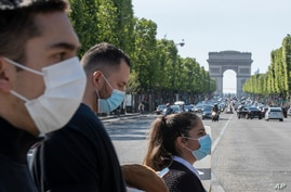 People wear face masks to help curb the spread of the coronavirus cross the Champs Elysees avenue in Paris, May 16, 2020, as France gradually lifts its Covid-19 lockdown.