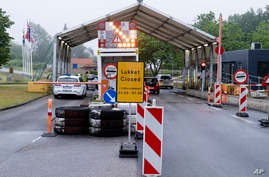 In this Saturday, June 13, 2020 photo, a sign with the opening hours of the border checkpoint between Harrislee in Germany and…