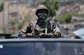An Indian army soldier guards atop one of the vehicles as an army convoy moves on the Srinagar- Ladakh highway at Gagangeer, north-east of Srinagar, India, June 17, 2020.