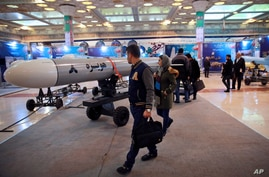 FILE - Visitors look at a cruise missile at a military hardware exhibit, at Imam Khomeini Grand Mosque, in Tehran, Iran, Feb. 3, 2019.
