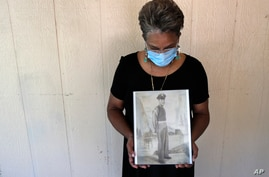 Belvin Jefferson White poses with a portrait of her father Saymon Jefferson at Saymon's home in Baton Rouge, Louisiana, May 18, 2020.