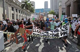 Demonstrators cross over a barricade as they march protesting the death of George Floyd in police custody, in Miami, Florida, May 31, 2020.