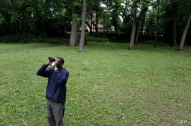 Keith Russell, program manager of urban conservation at Audubon Pennsylvania, looks through binoculars while conducting a breeding bird census, at Wissahickon Valley Park in Philadelphia, June 5, 2020.