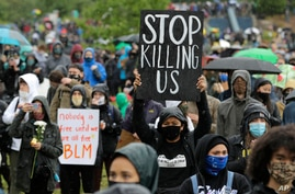 """FILE - A protester holds up a sign that reads """"Stop Killing Us,"""" during a """"Silent March"""" against racial inequality and police brutality, in Seattle, Washington, June 12, 2020."""