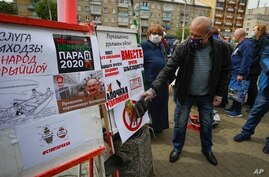 FILE - A man uses a slipper to slap a poster that shows a portrait of Belarusian President Alexander Lukashenko as people gather signatures in support of potential presidential candidates in upcoming presidential elections in Minsk, Belarus, May 24, 2020.