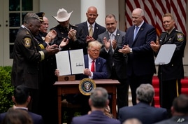 President Donald Trump holds up an executive order on police reform after signing it in the Rose Garden of the White House, in Washington, June 16, 2020.