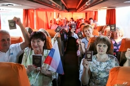 People travelling to Russia show their Russian passports at a bus stop in Donetsk, eastern Ukraine, June 27, 2020.