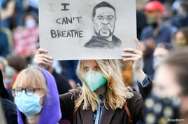 FILE - A demonstrator wearing a protective mask holds up a placard as she attends a protest against racial injustice, following the death of George Floyd at the hands of police in Minneapolis, in Amsterdam, Netherlands, June 10, 2020.