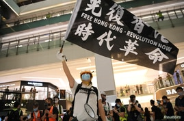 A pro-democracy activist waves a banner during a protest at the New Town Plaza mall in Hong Kong, June 12, 2020.