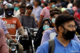 FILE - A woman wearing a face mask rides as a passenger on a motorbike amid a rush of people outside a market, amid the coronavirus pandemic, in Karachi, Pakistan, June 8, 2020.